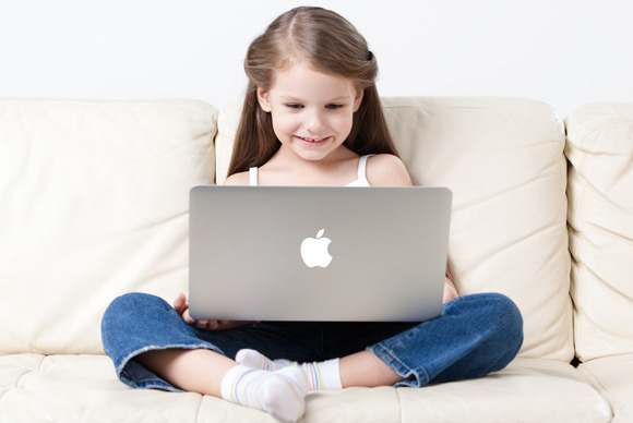 Kid sitting in front of Mac screen